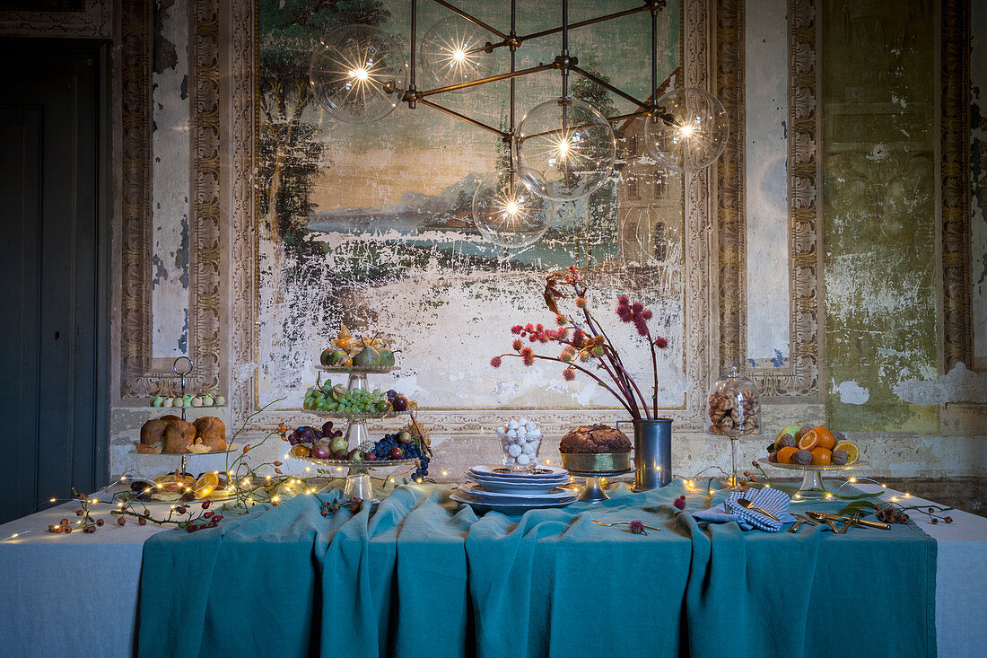 A Christmas buffet with fairy lights against a wall with a fresco
