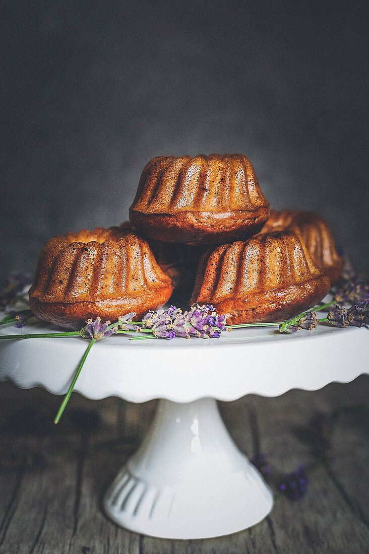 Mini Bundt cakes with blackberries and lavender on a cake stand