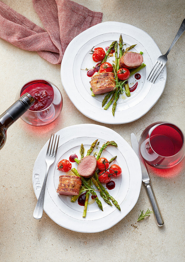 Herb lamb eye of loin with bacon, green asparagus and oven-roasted vegetables