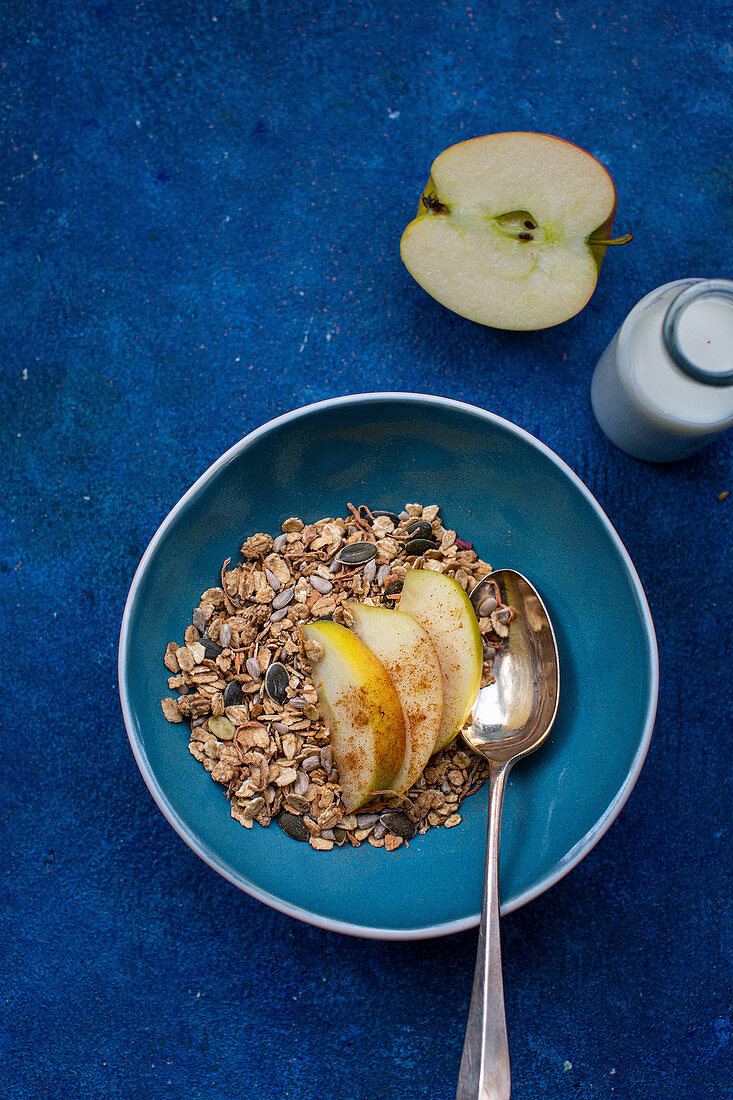 Muesli with apple wedges on a blue plate on a blue surface