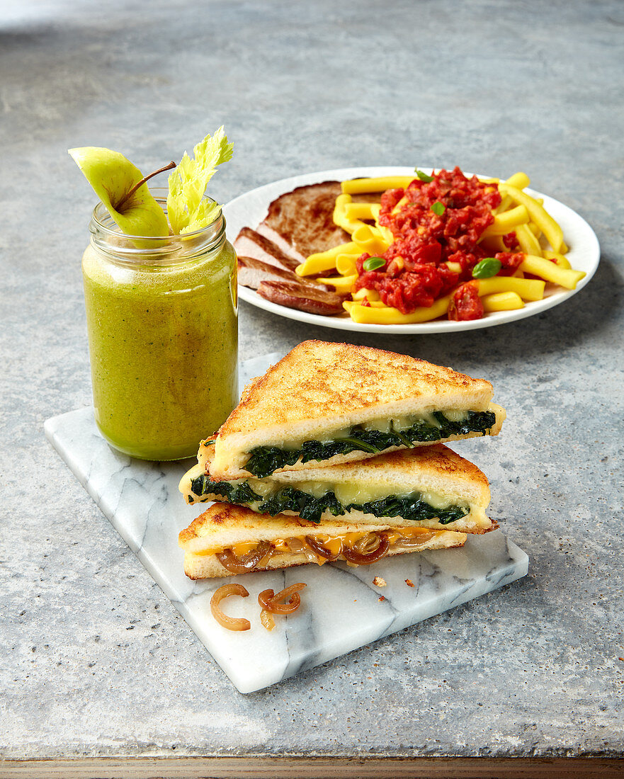 A toasted sandwich, an apple and celery smoothie and pasta with tomato sauce
