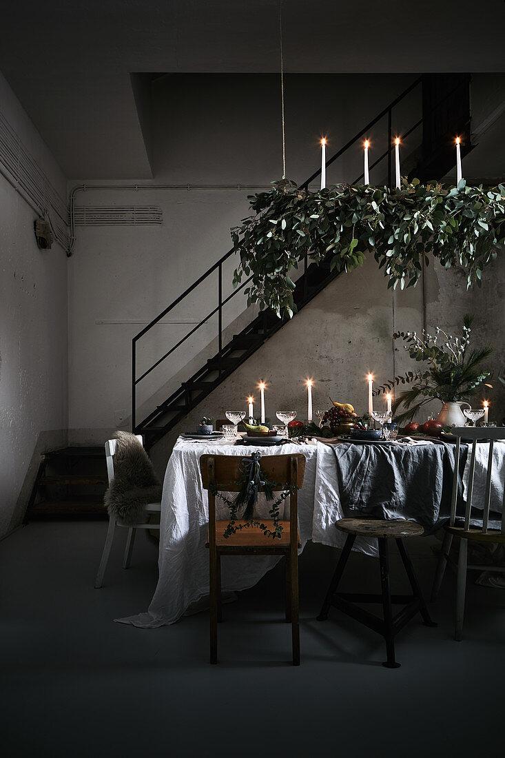 Weihnachtlich dekorierter Esstisch bei Kerzenschein im Loft-Ambiente