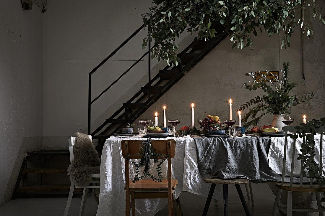 Esstisch weihnachtlich dekoriert bei Kerzenschein im Loft-Ambiente