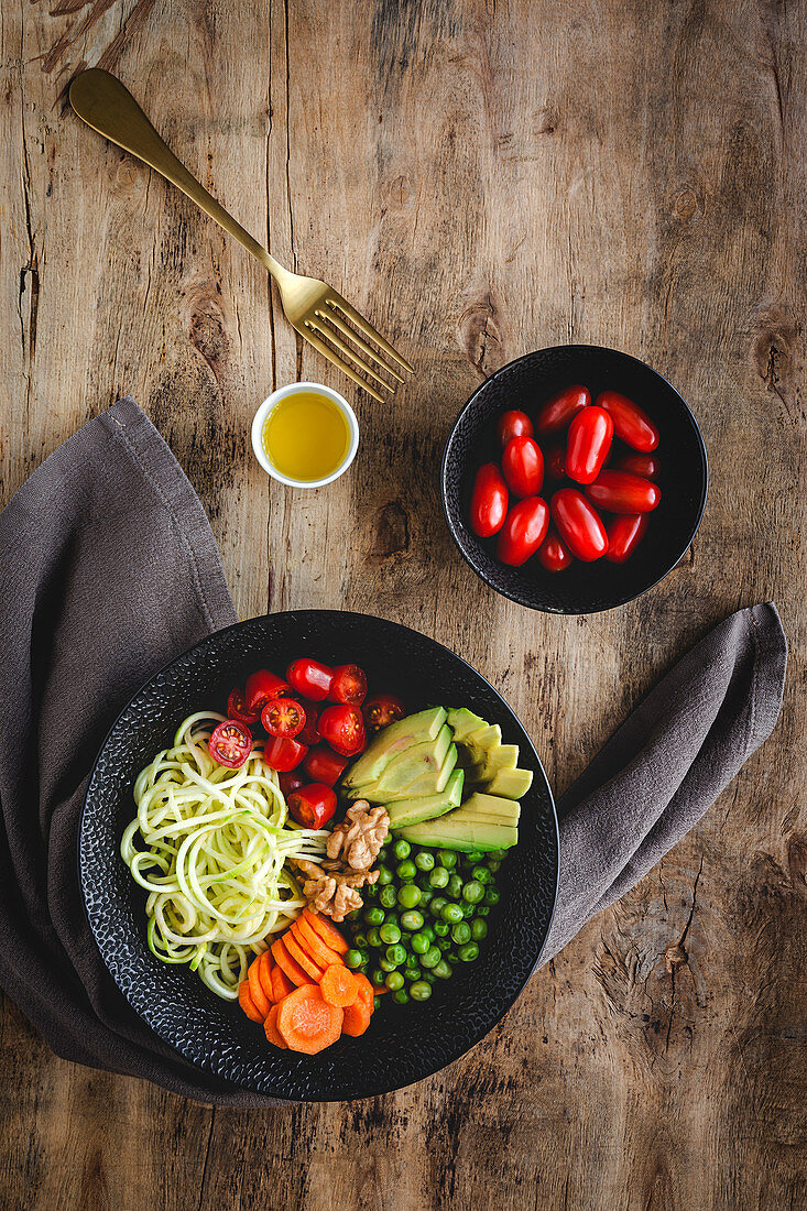 Zucchini raw vegan pasta with peas, cherry tomatoes and avocado