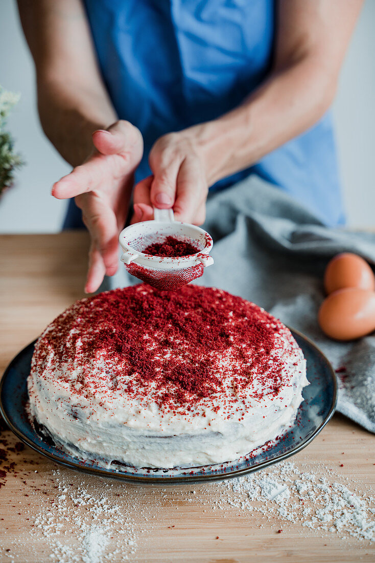 Unrecognizable person spilling bright powder on red velvet cake while cooking on table in kitchen