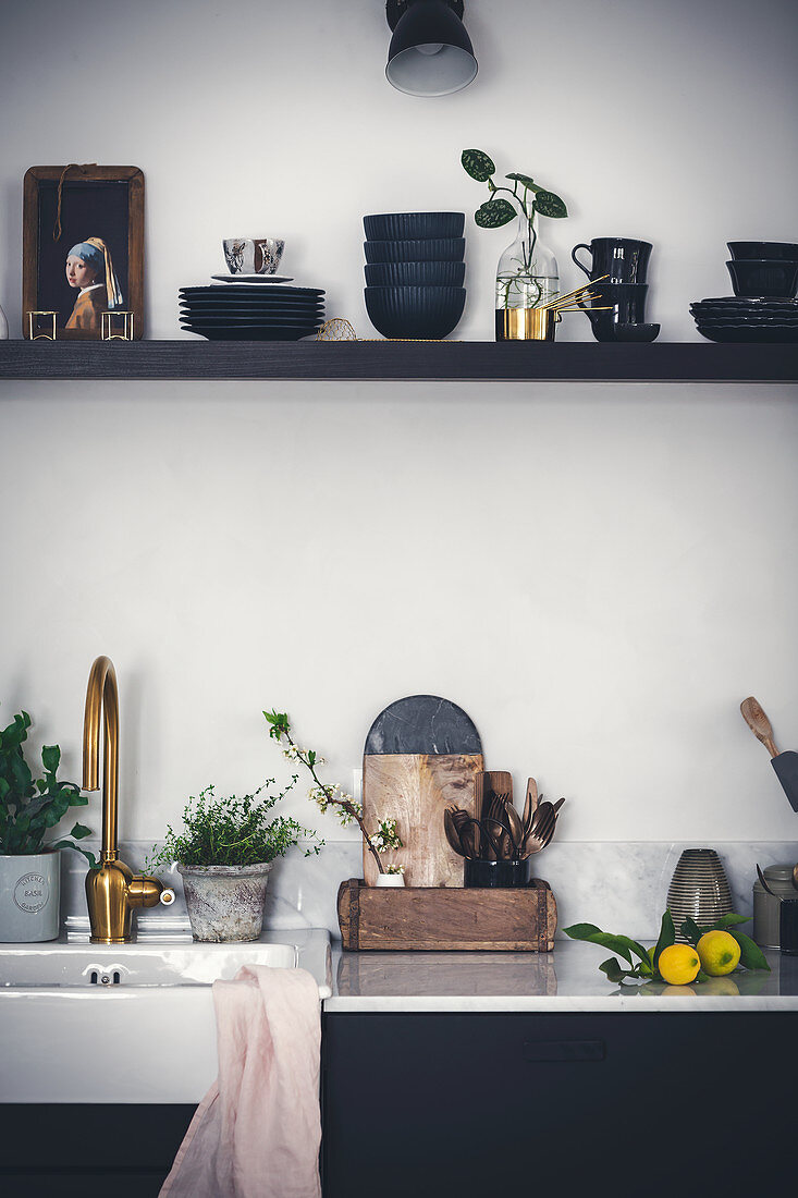Utensils and ornaments on shelf above kitchen sink with golden tap fitting