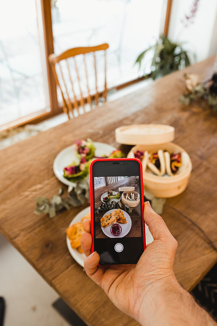 Hand of person using smartphone and taking photo of various dishes placed together on wooden table