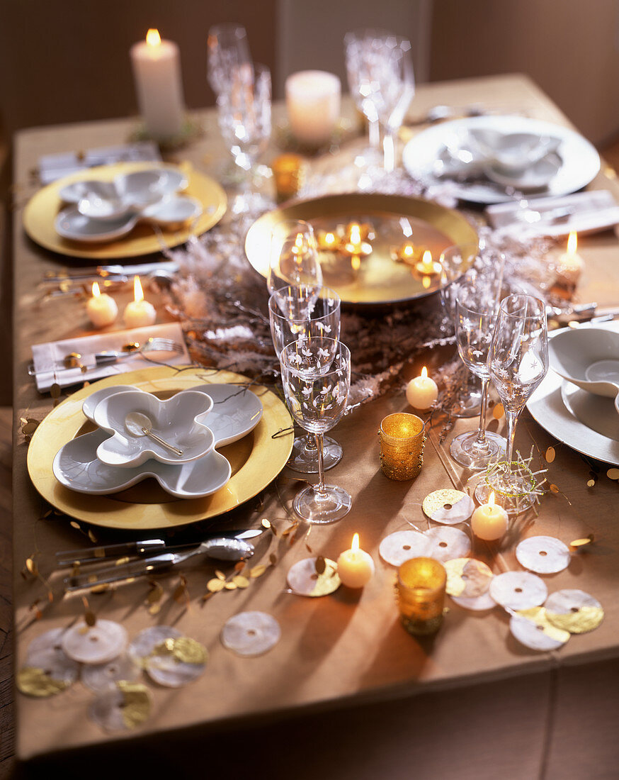 Festive table laid in white and gold with candle decorations