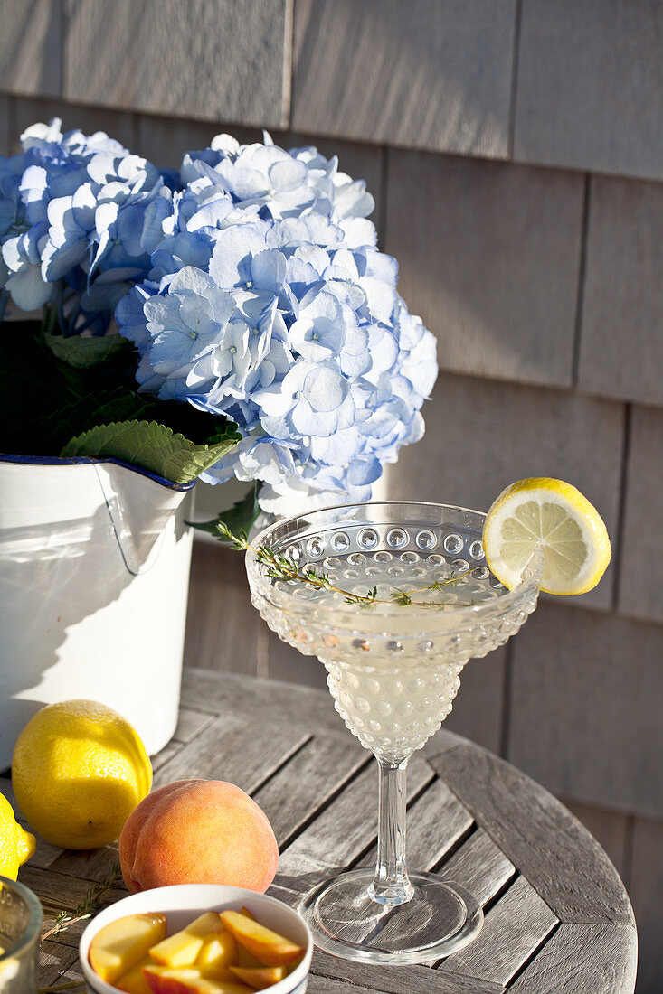 An outdoor table with lemonade with vodka, a sprig of thyme, lemons and peaches