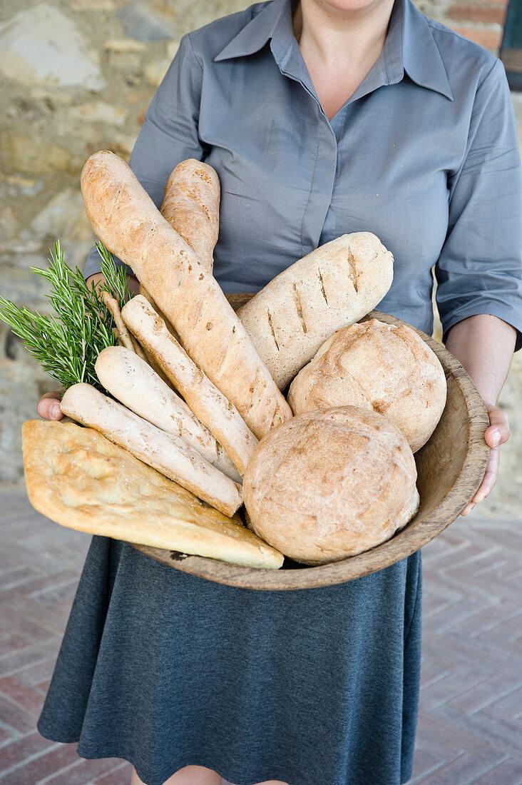Girl holding a basket of various freshly baked homemade breads