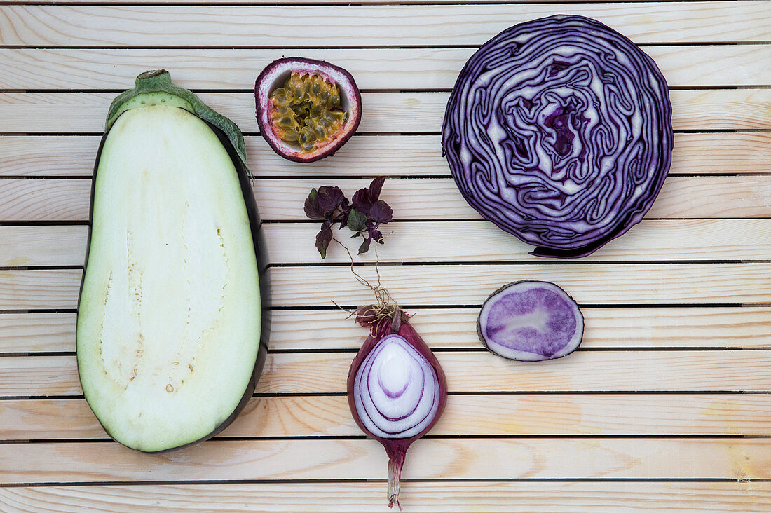 Flatlay of purple fruits and vegetables arranged on a wooden background