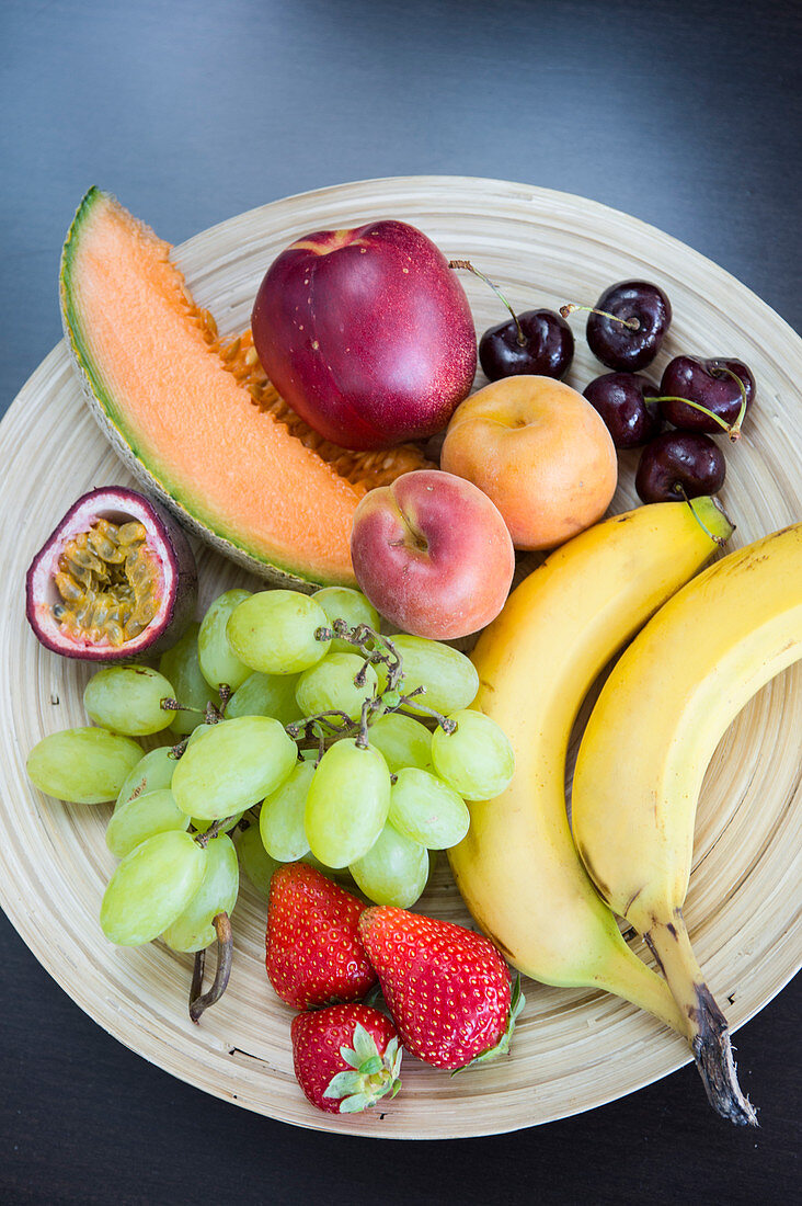 Plate of fresh colorful fruits on a bamboo plate