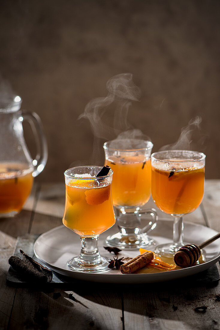 Hot mulled apple juice with spices, cinnamon, cloves, star anise, orange slices and zest