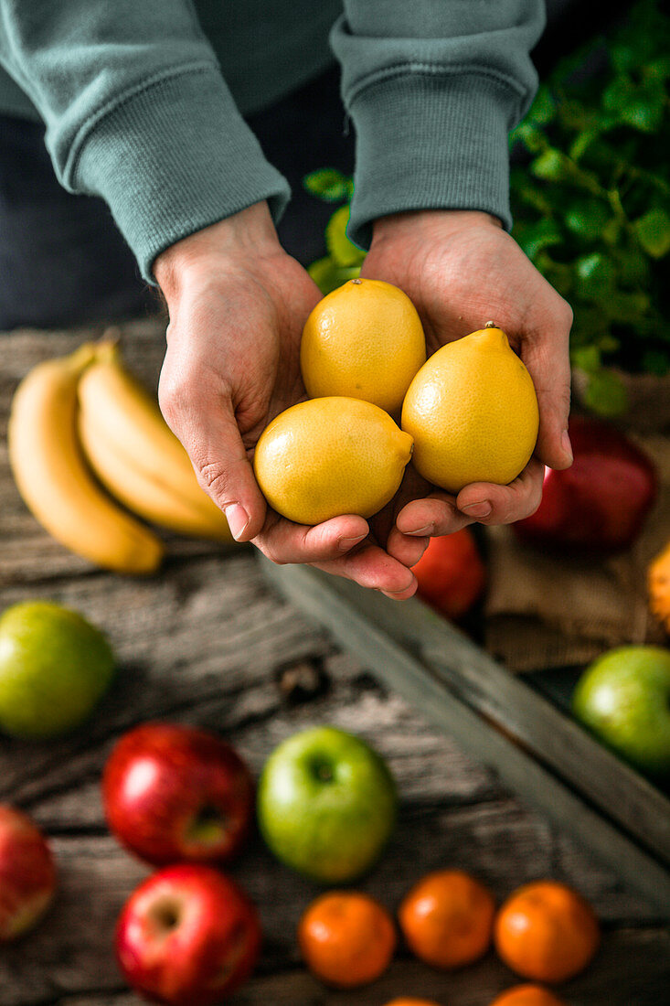 Farmer holding harvested fruit and vegetables