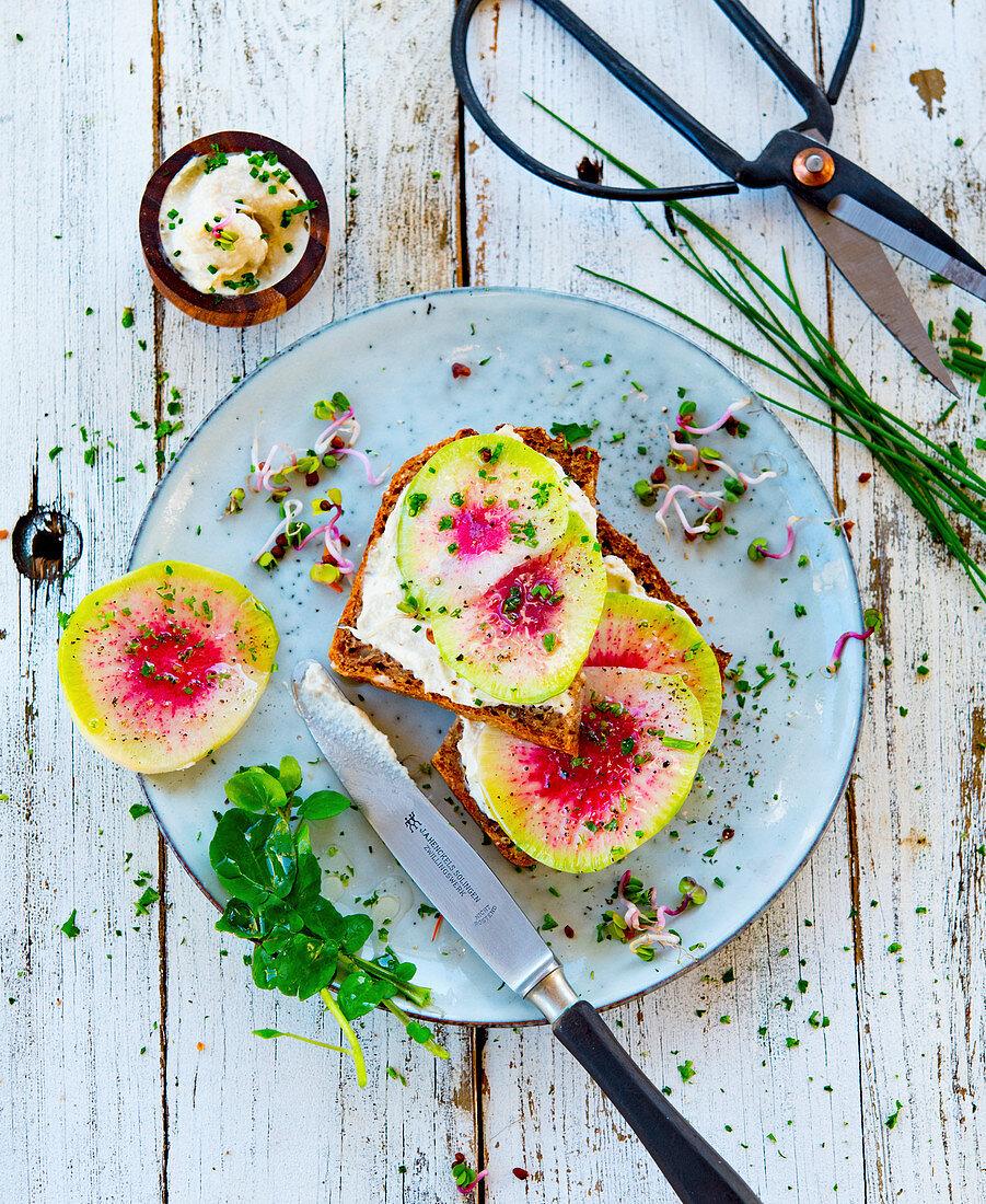 Sliced watermelon radish on wholemeal bread
