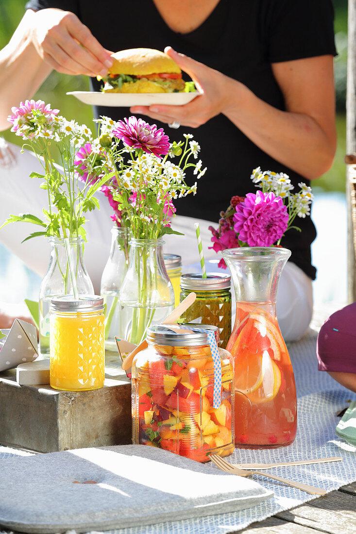 Sommerliches Picknick mit Getränken, Obstsalat und Burger