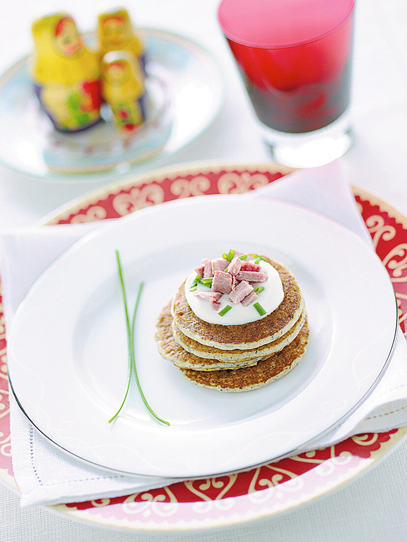 Blinis with sour cream, ham and chives