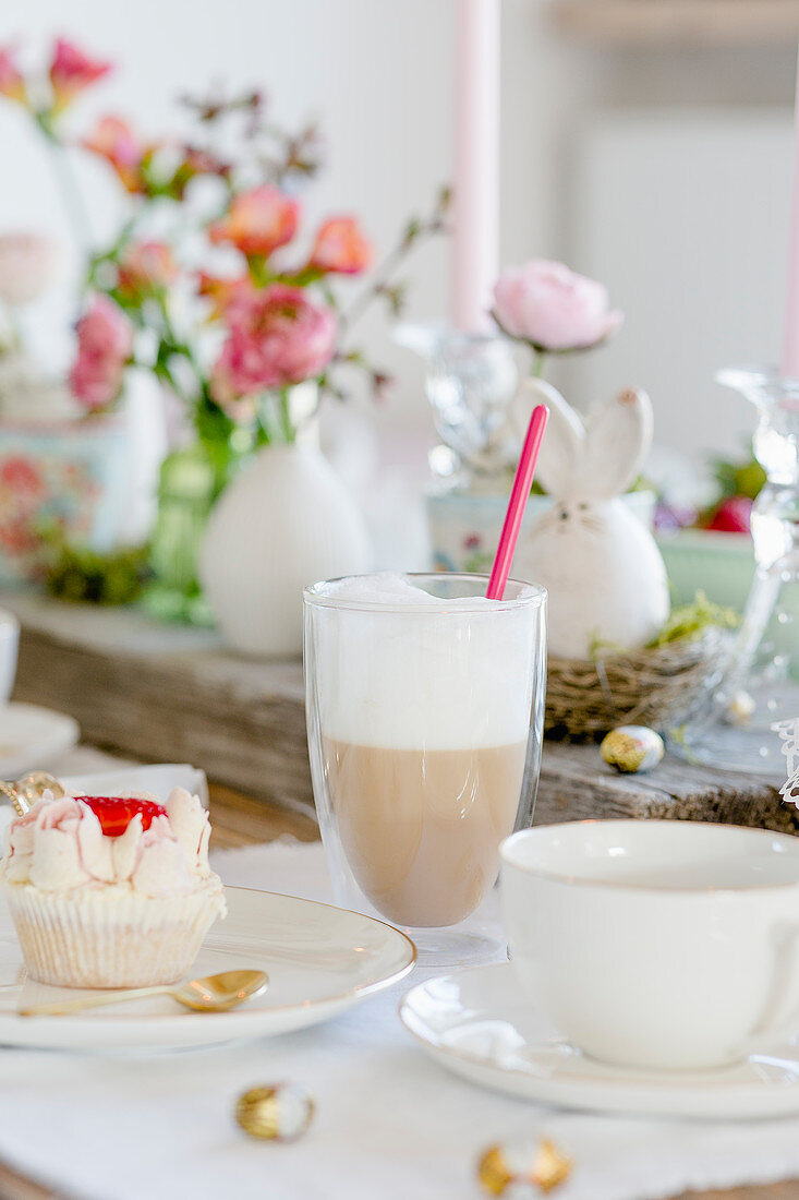 Latte macchiato and a cupcake on a table laid for Easter