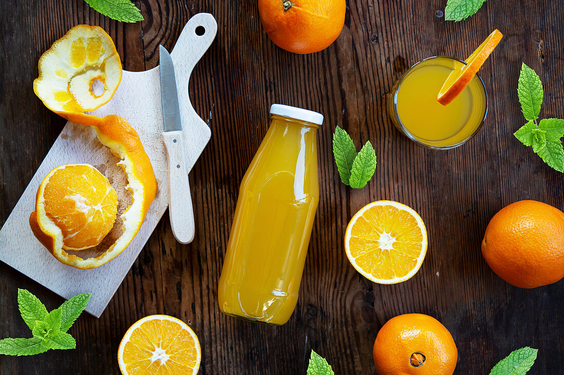 Orange juice in a glass and bottle with fresh oranges and mint leaves