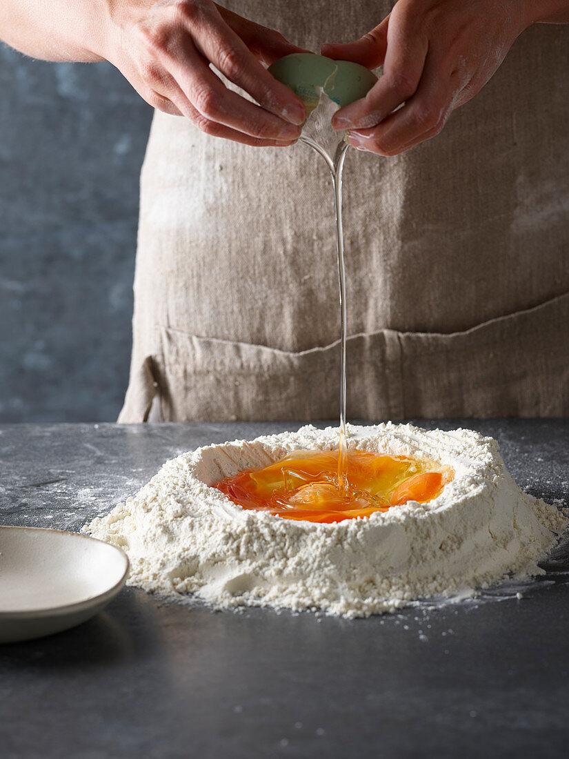 Preparing pasta dough: crack eggs into a flour well