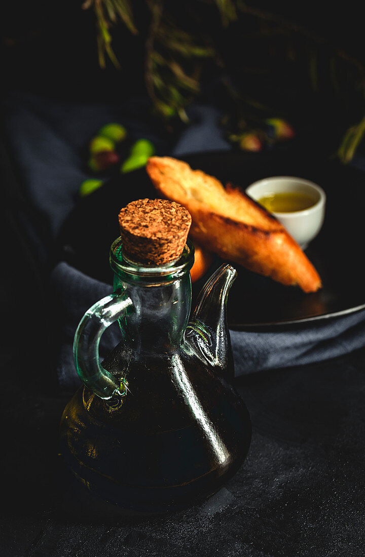 Fresh Spanish extra virgin olive oil with olives and old olive branch on dark background Healthy food Mediterranean diet. Vegan. Vegetarian. Toasted bread