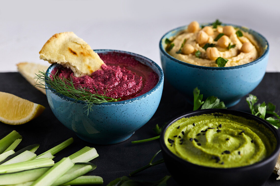 Various types of hummus served with fresh vegetables and pita bread