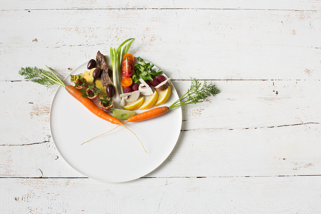 A symbolic image of keto cuisine: a clock made of vegetables, fruit, mushrooms and meat