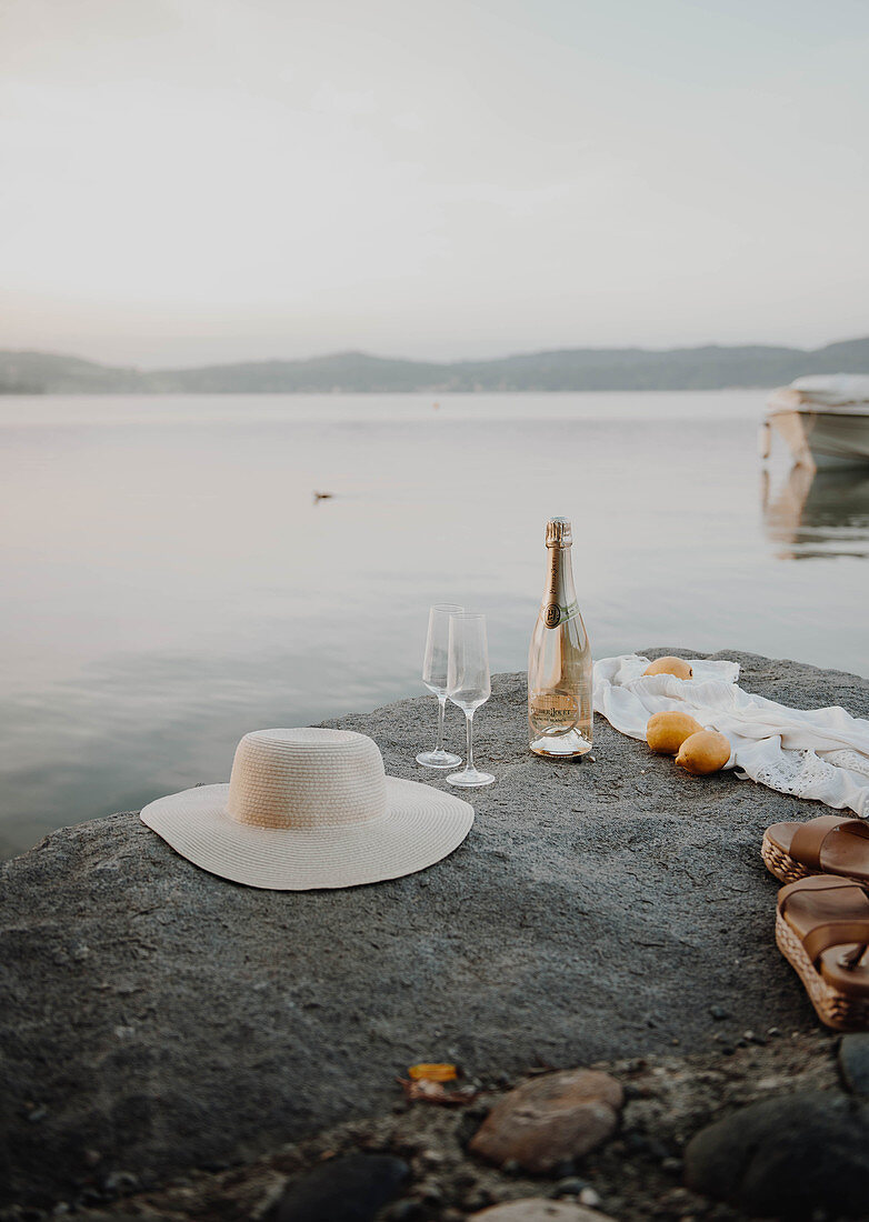 Hat, bottle of Champagne, glasses and lemons on rock next to sea