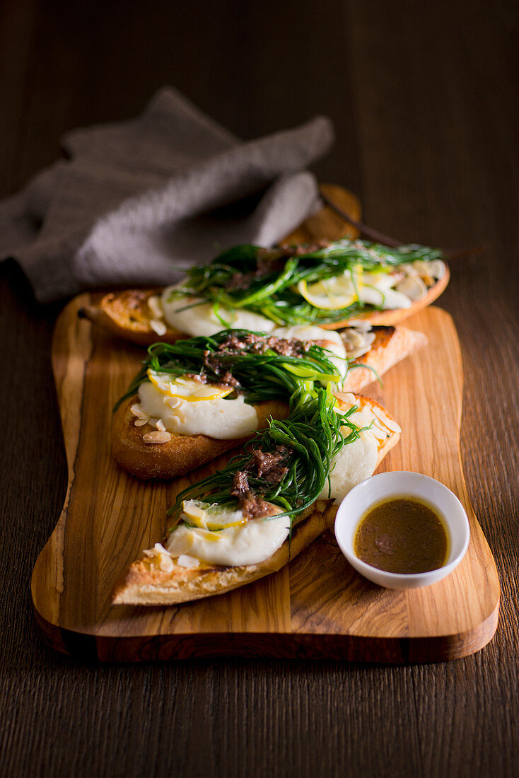 Grilled baguette slices with mozzarella, opposite-leaved saltwort and anchovy sauce