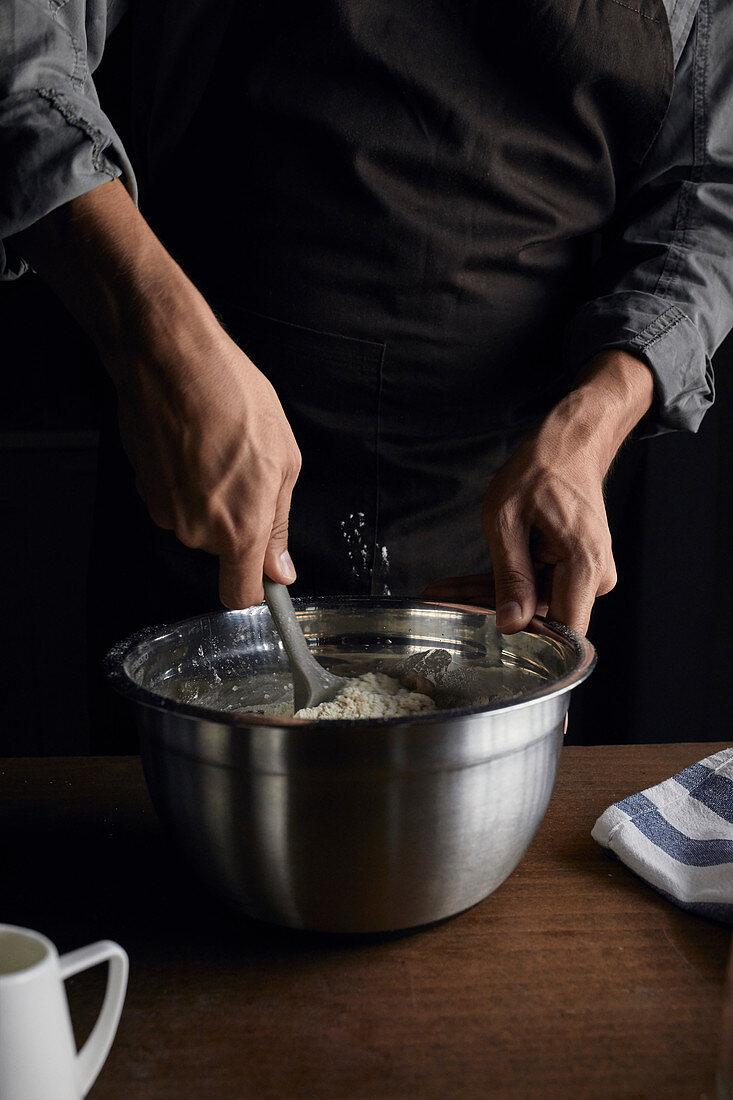 Mixing sourdough with spatula