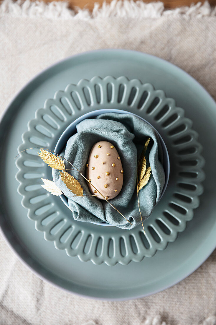 Egg with golden beads on blue-grey plate and napkin