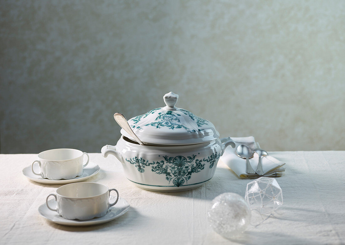 Soup bowls and a soup tureen on a white tablecloth decorated with glass balls