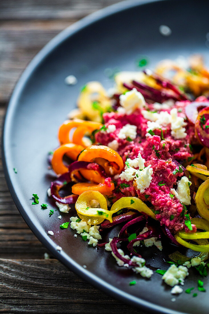 Vegetable noodles made from sweet potatoes with carrots, beetroot pesto and feta cheese