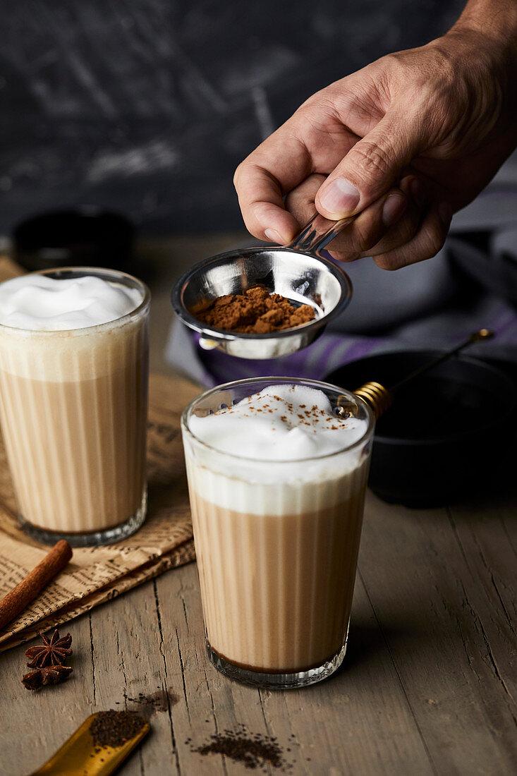 Cinnamon powder being sprinkled on chai lattes