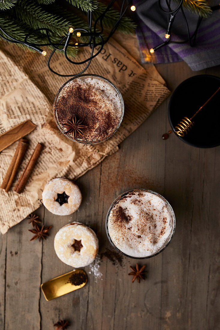 Chai latte in glasses with milk foam, cinnamon and anise stars