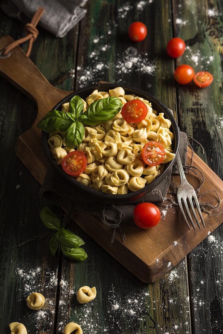 Homemade ravioli with cut cherry tomatoes and fresh basil