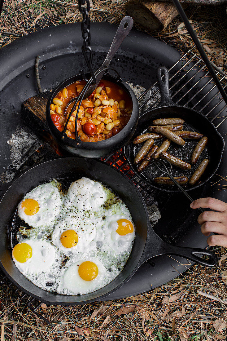 Camping breakfast beans with sausages and fried eggs