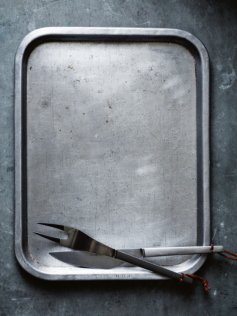A baking tray with carving cutlery