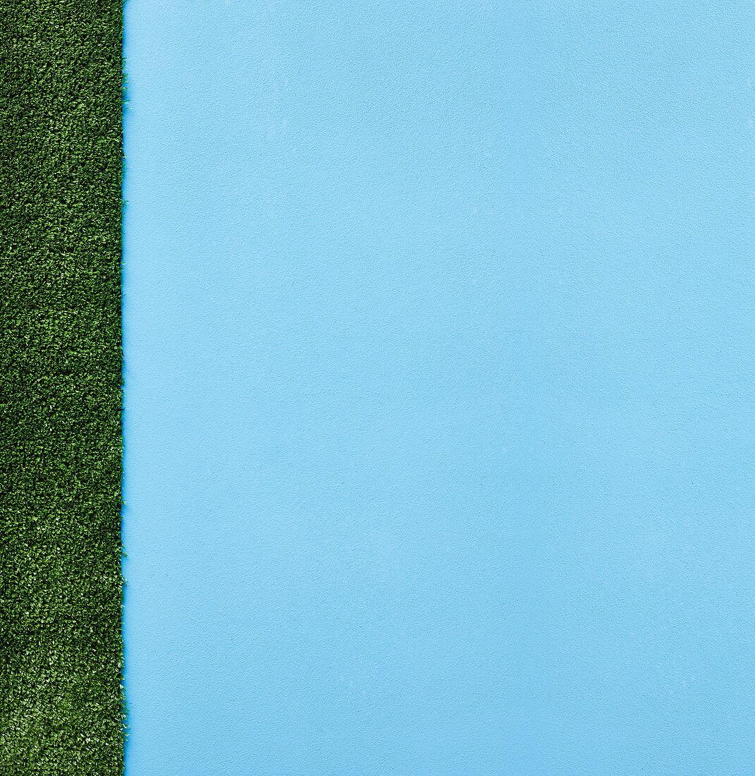 A light-blue background with artificial grass