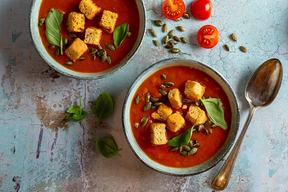 Vegetarian Vegan Tomato and Lentil soup with croutons and toasted pumpkin seeds and basil