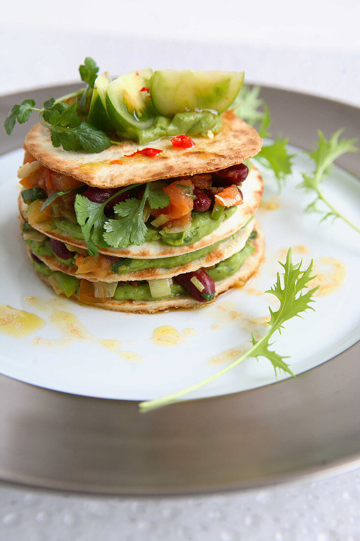 Tortilla millefeuille with guacamole and tomatoes