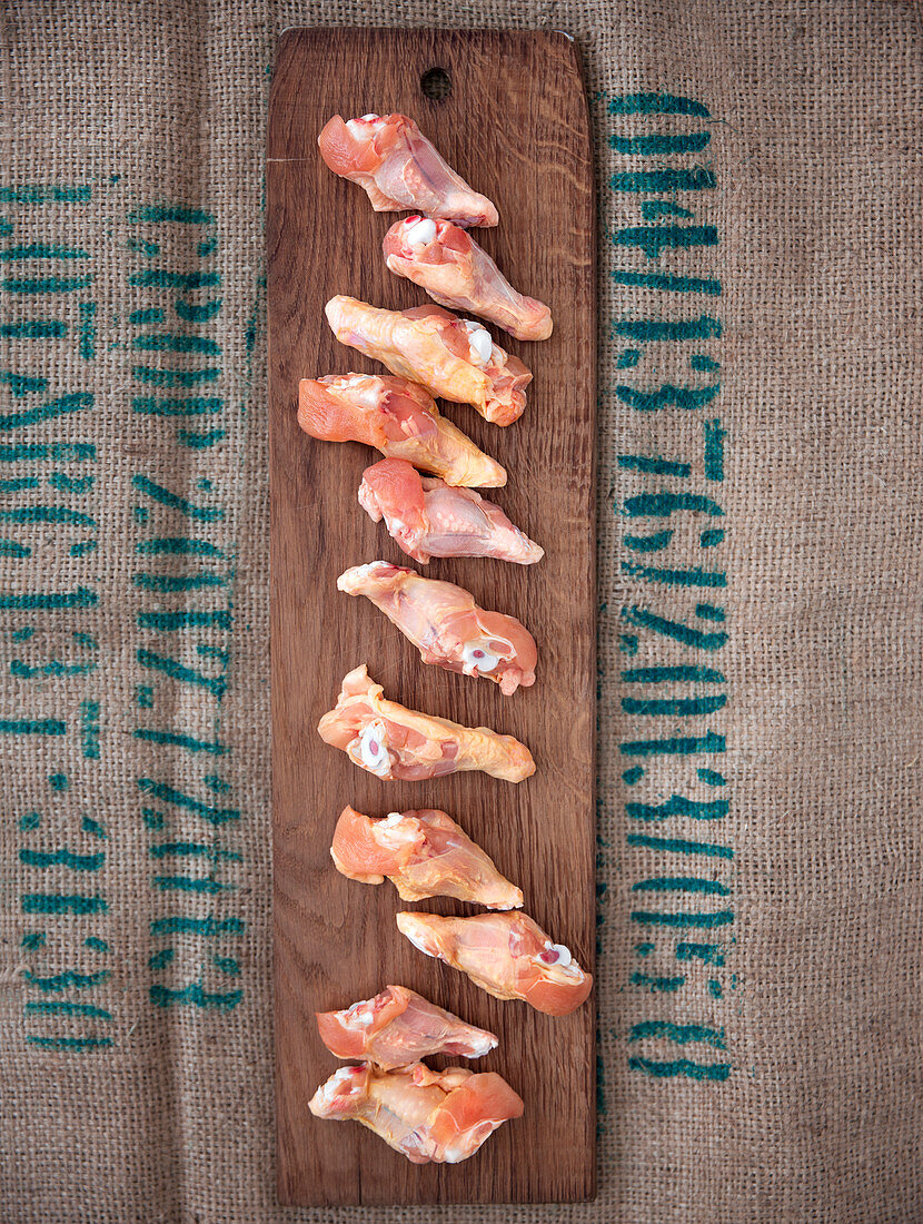 Raw chicken wings on a wooden board
