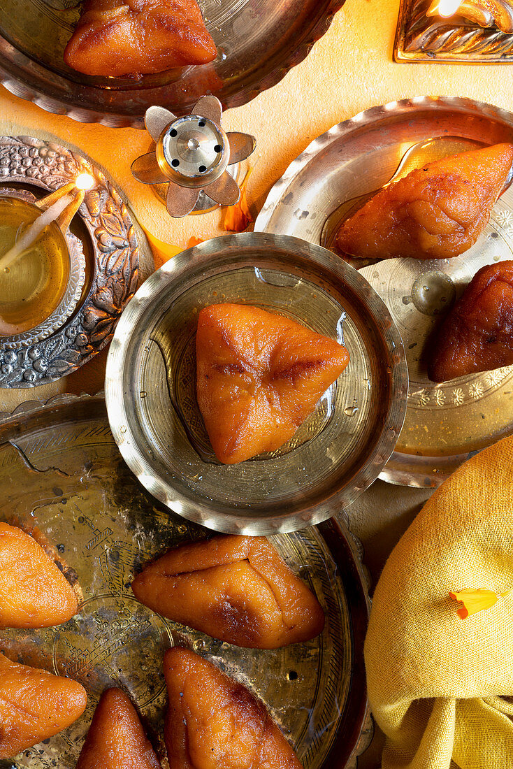 Diwali Special - Sweet Potato Dumplings with Indian traditional brass candles, yellow napkin, flowers