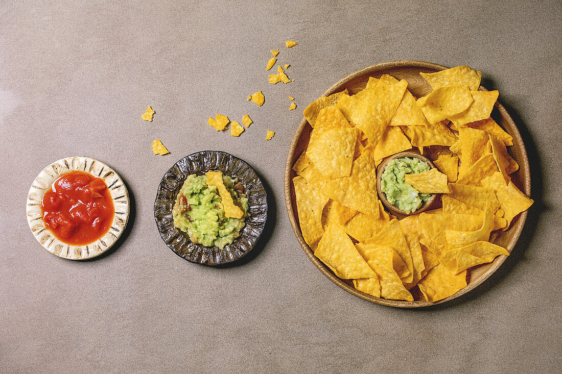 Tortilla nachos corn chips with avocado guacamole and tomato sauce served in wood plate