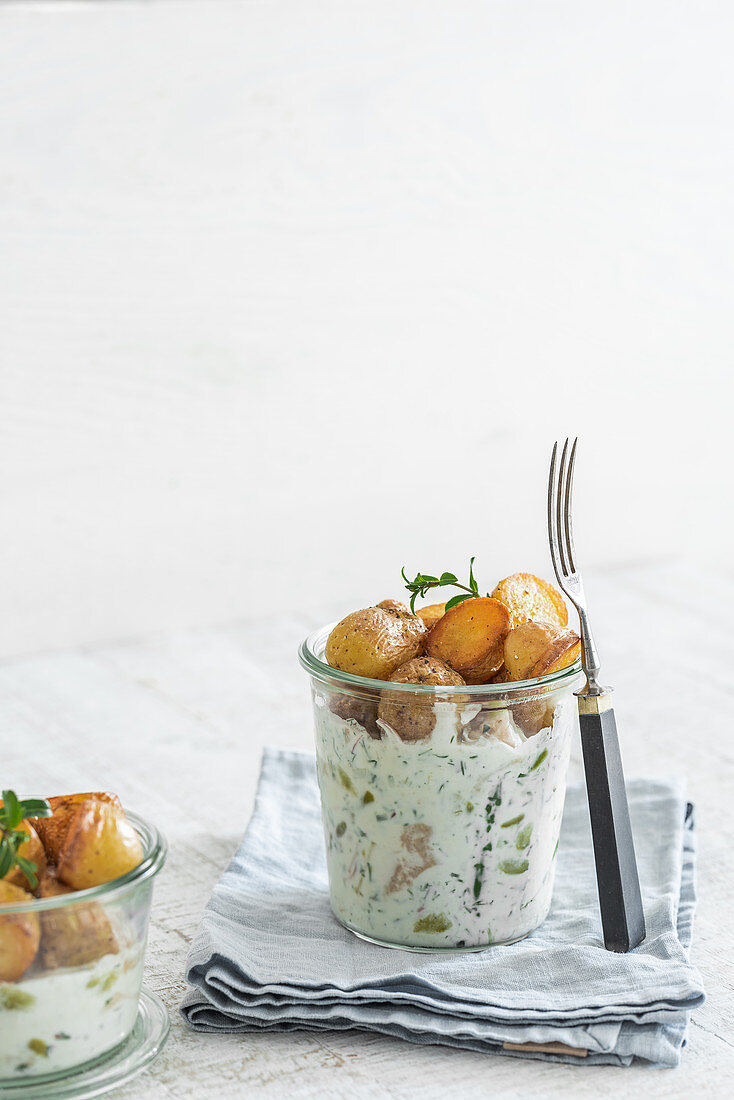 Herring salad in glasses with small roasted potatoes