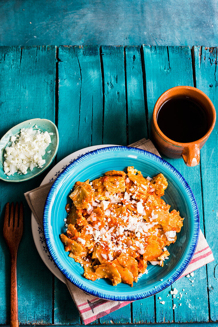 Mexican fried corn chips with scrambled eggs, tomatoe and chilli sauce, cheese, and onions, topped with fried eggs, served with coffee