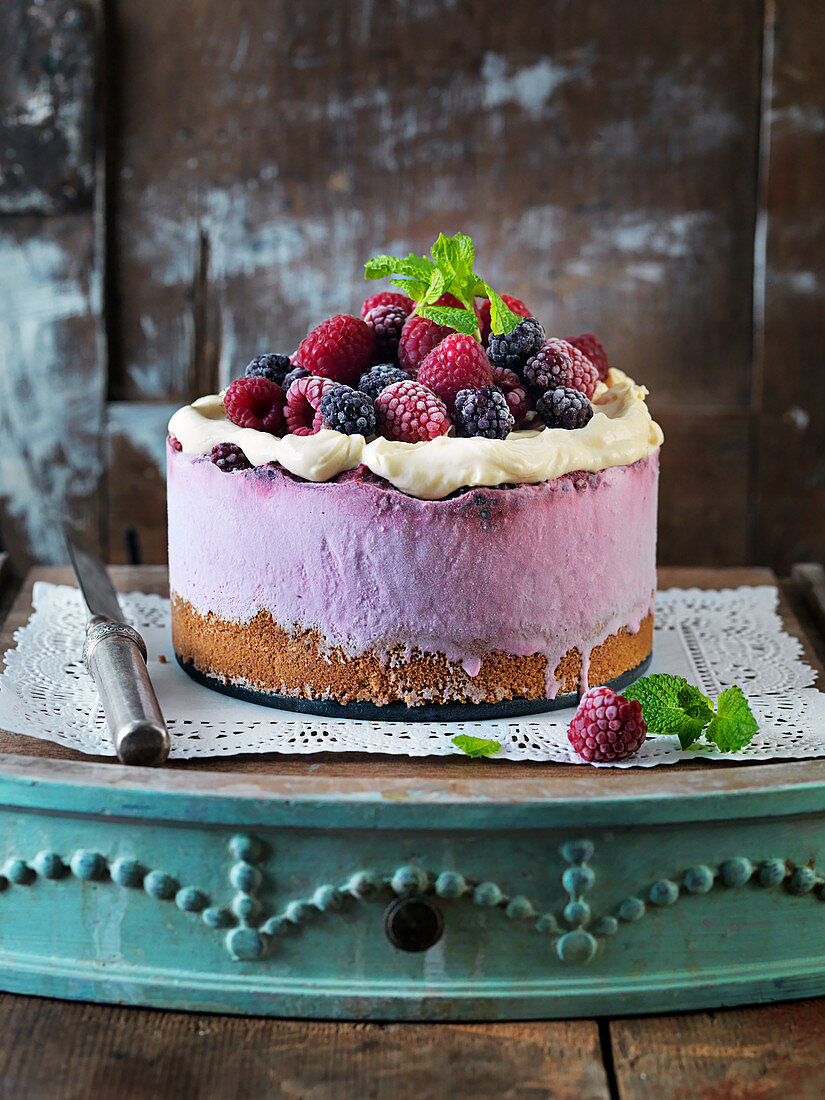 No Bake Cheescake with rapberries, frosting, mint and blackberries