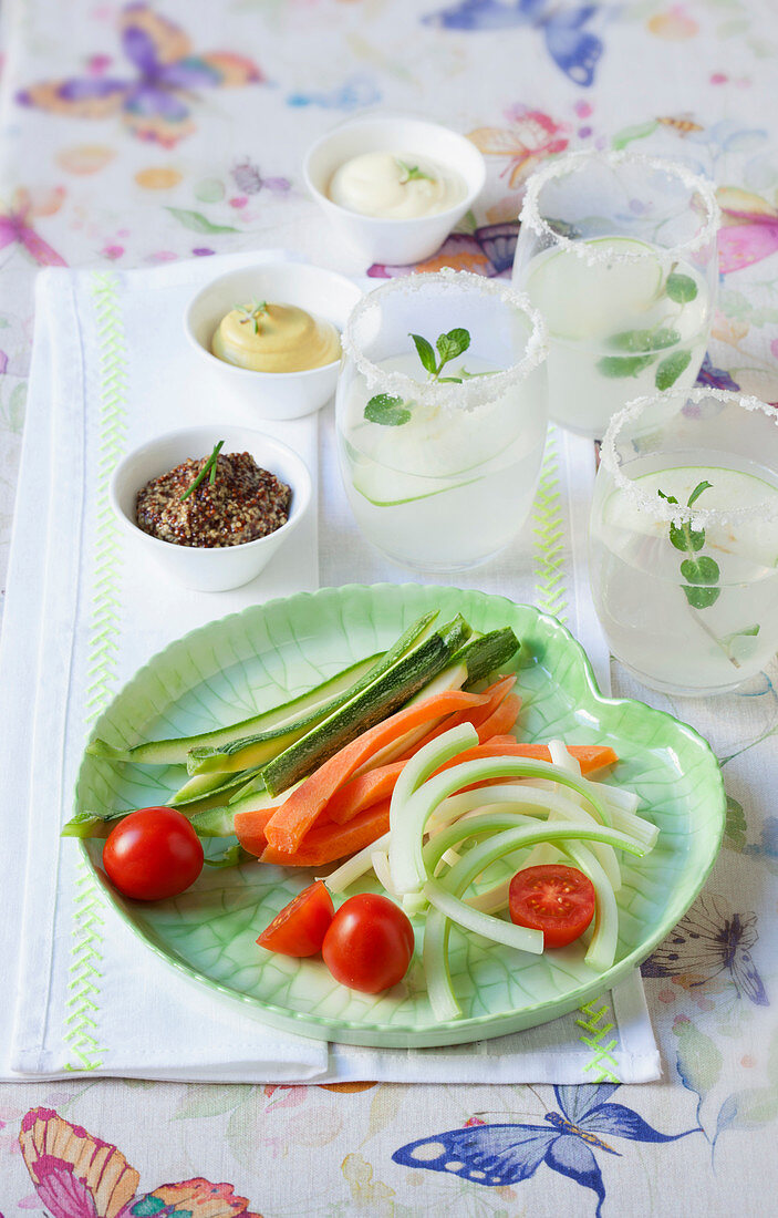 Ice-cold mint-lime cocktails, vegetables sticks and sauces