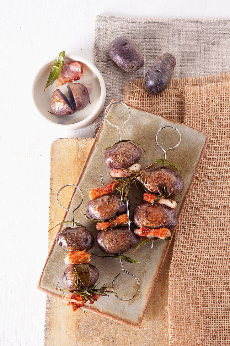 Potato kebabs with bacon, laurel and rosemary