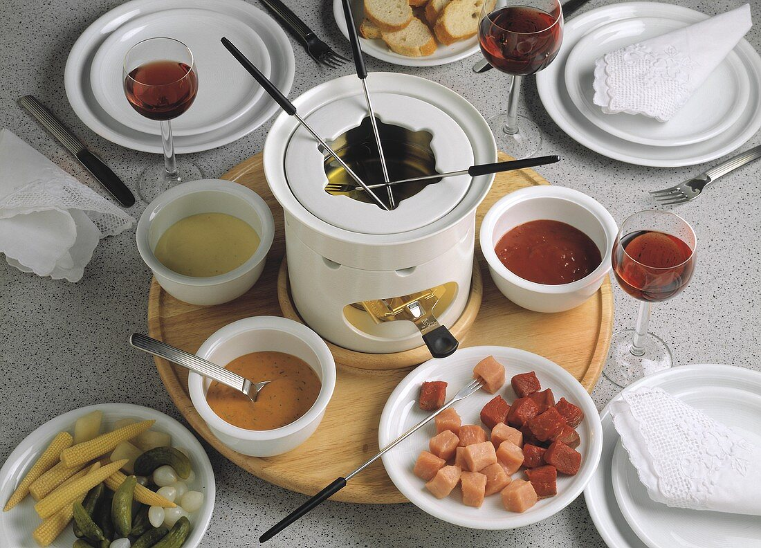 Fondue with meat, mixed pickles and various sauces